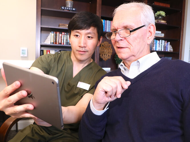 a male geriatric care manager showing and senior man information on an ipad