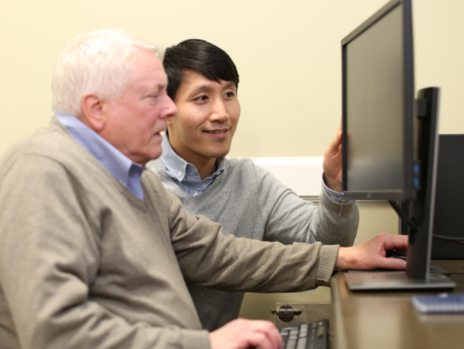 park place volunteer teaches male senior resident to use computer