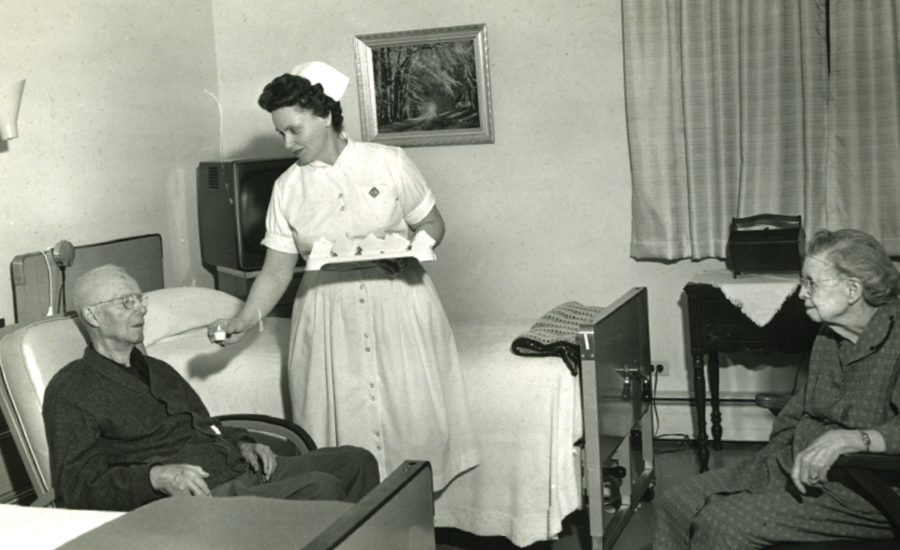 a nurse from the 1960s gives medicine to a senior male resident as his wife looks on
