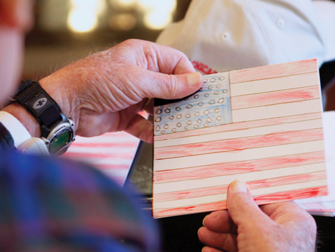 resident holds card with child's drawing of American flag