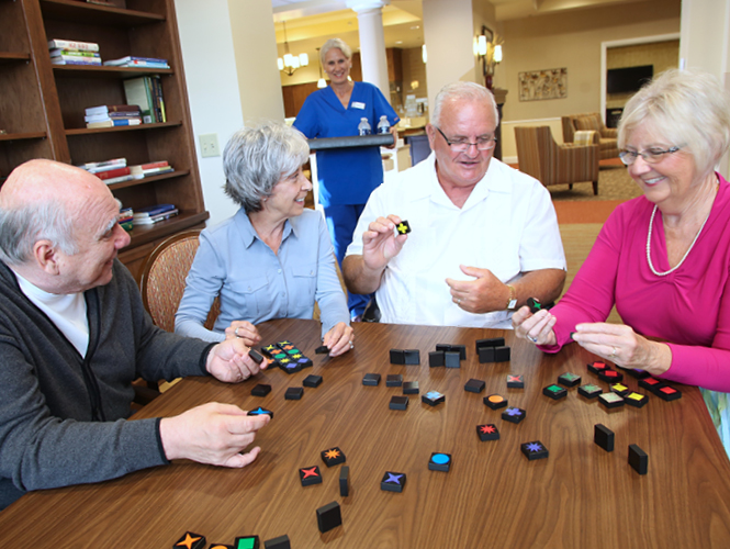 female staff brings refreshments to resident playing games