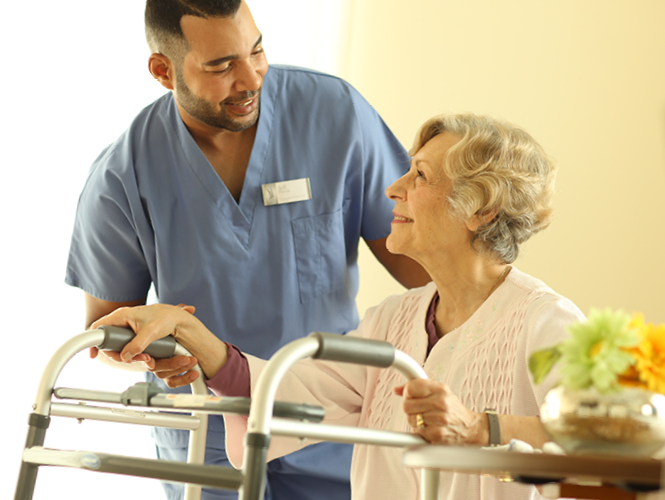 A male cna assists senior resident with using walker