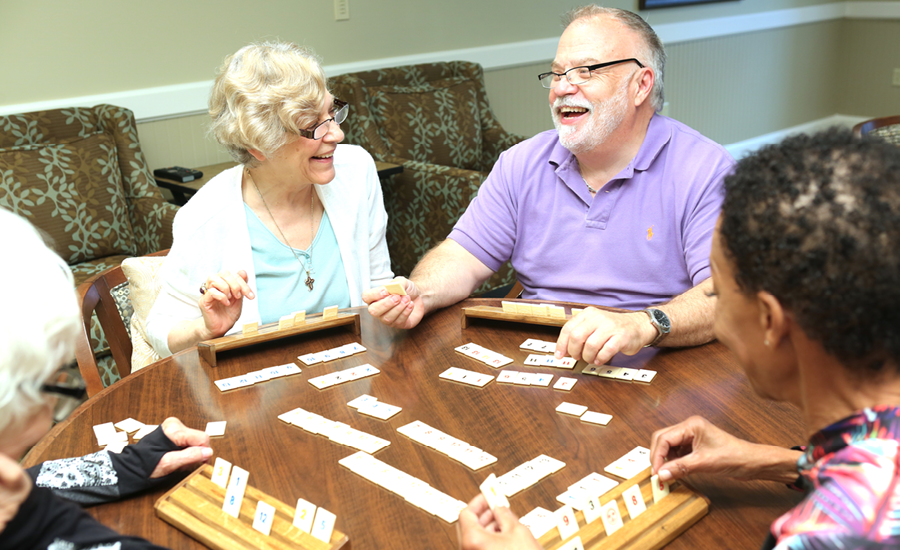 table of royal park place resident laugh together as they place rummikub