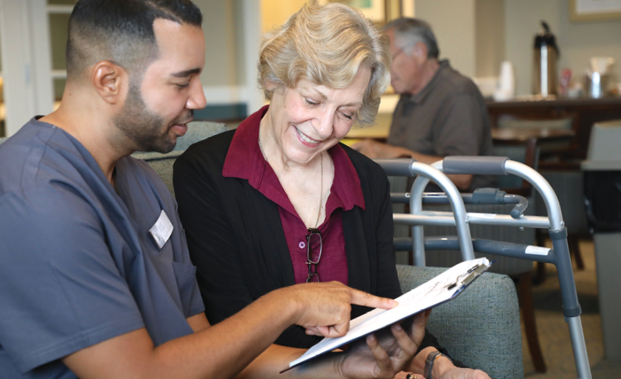 Male healthcare manager talks with a senior woman about her care