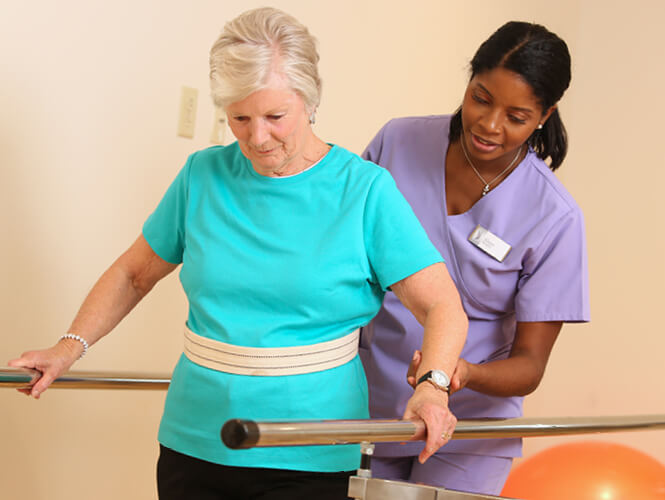 rehab therapist assists senior woman with gait belt
