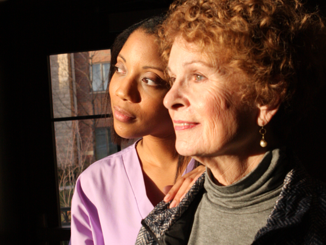 a providence hospice cna stands with one of her palliative care patients