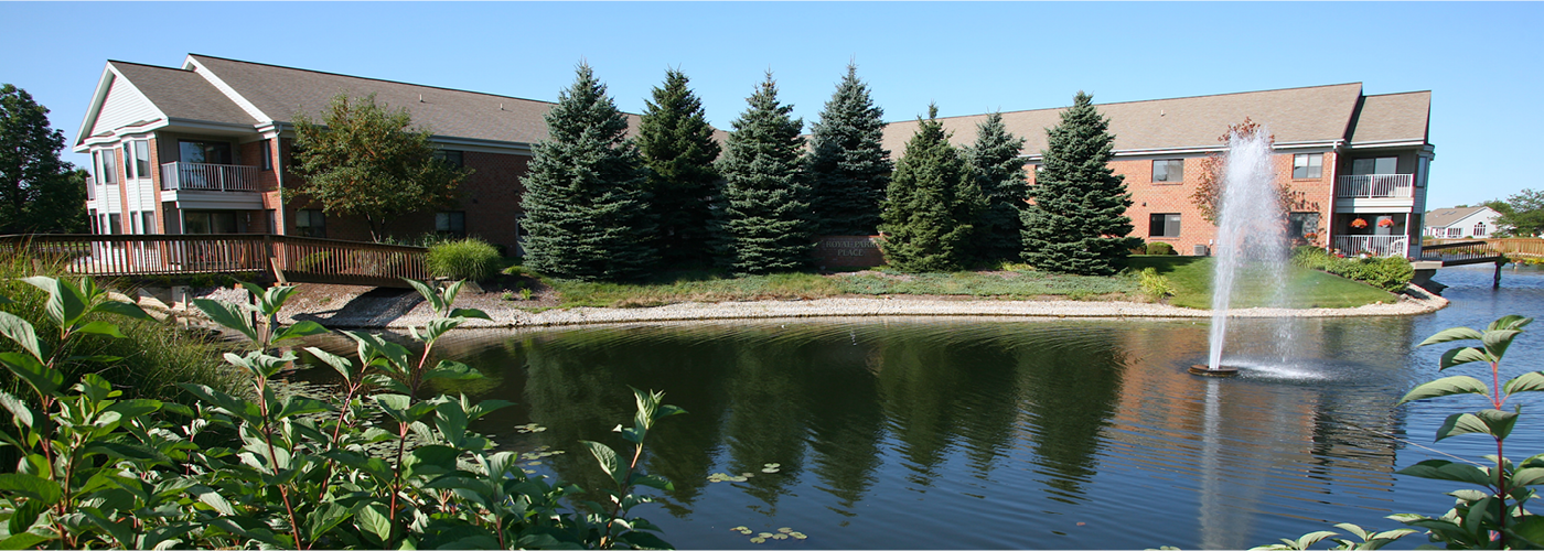 exterior shot of royal park place and lovely lake surrounding campus