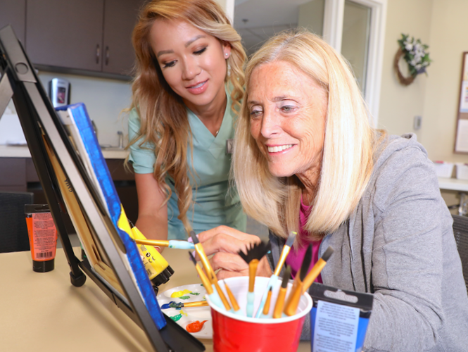 female CNA assists senior female Saratoga grove resident with art project