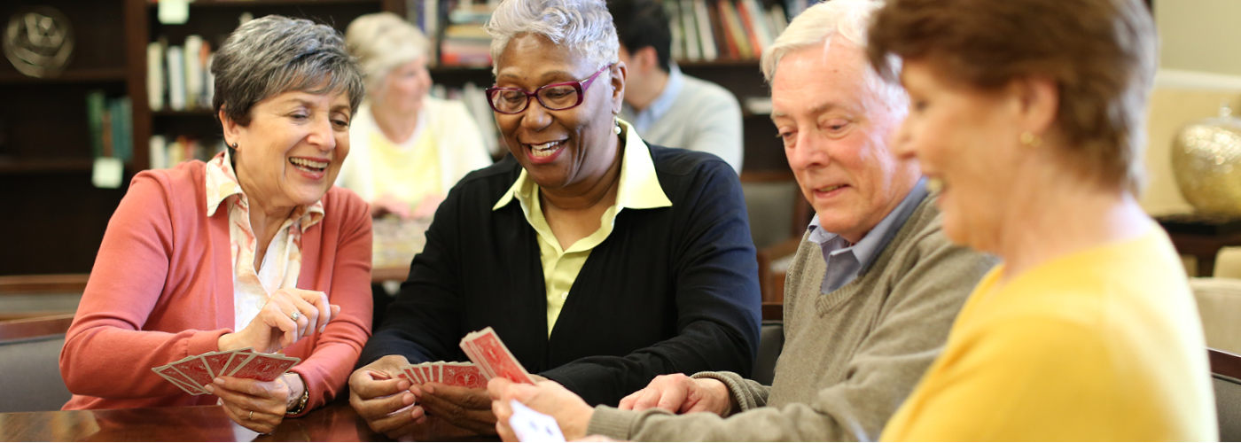 Friends play a game of cards at Saratoga Grove Assisted Living and Retirement Living