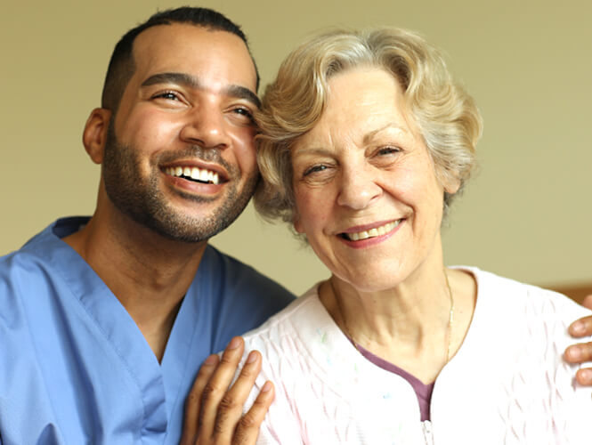 a male CNA and an elderly woman smiling