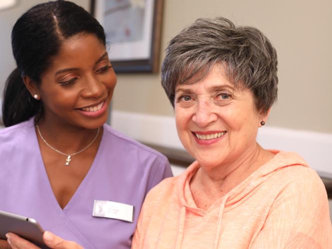 a female CNA and a senior respite client smile together