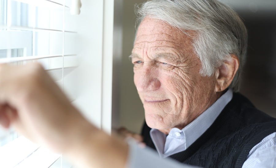 senior man looks out window blinds