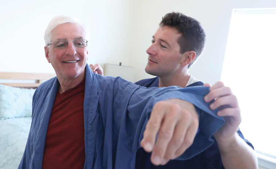 male cna assists transition to home patient with his robe