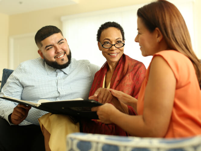 A young man and his senior mom look at a booklet with a female healthcare staff