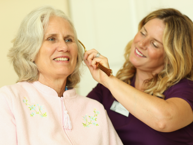 a CNA helps care for senior female's hair