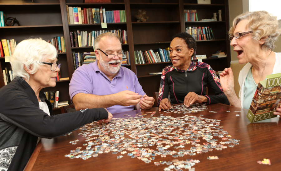 four senior park place residents work on puzzle together