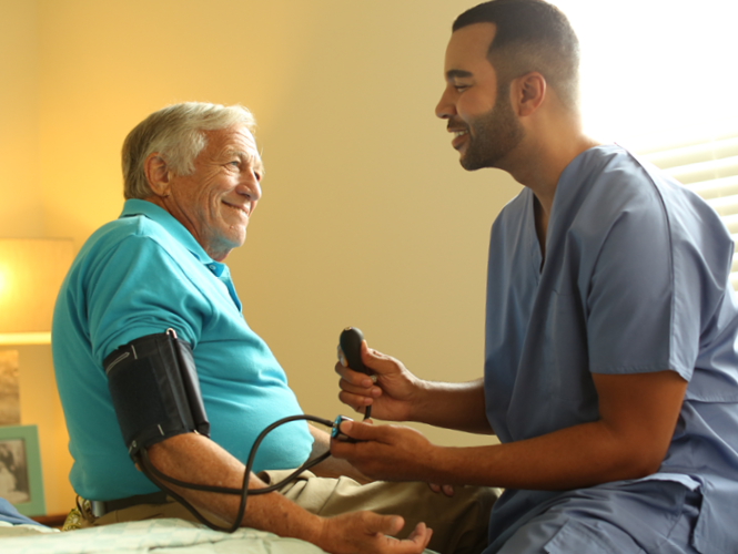young male healthcare worker takes senior man's blood pressure