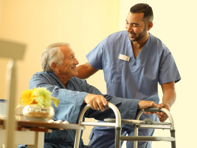 Male CNA helps senior man stand with his walker