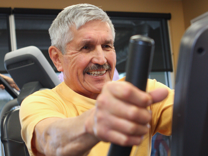 senior resident smiles as he exercises