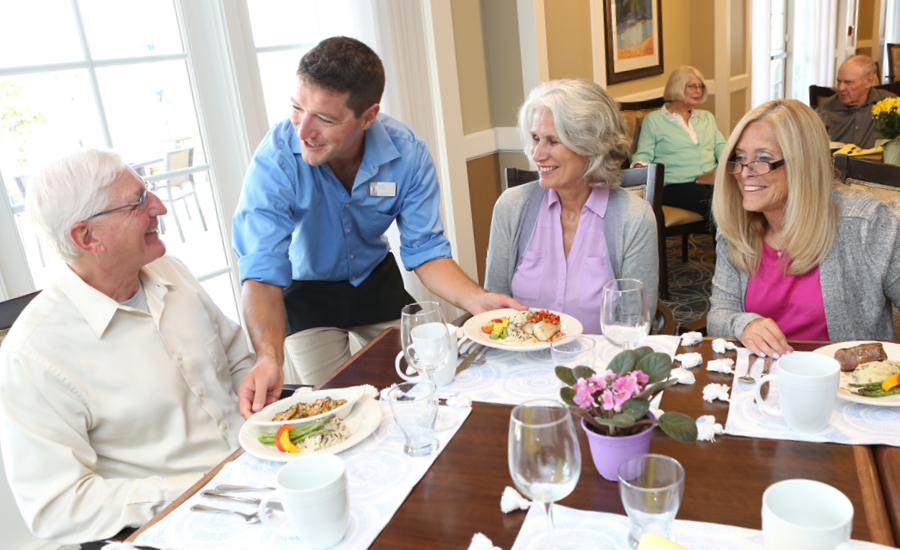three senior park place residents are served restaurant-style lunch by waiter