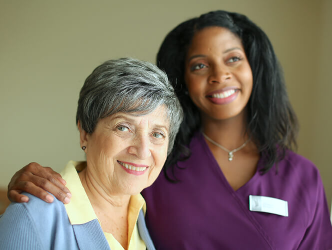 a female resident aide and an elderly woman smiling