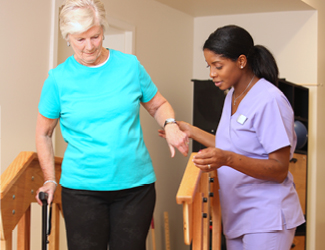 female CNA assists senior female with balance bars