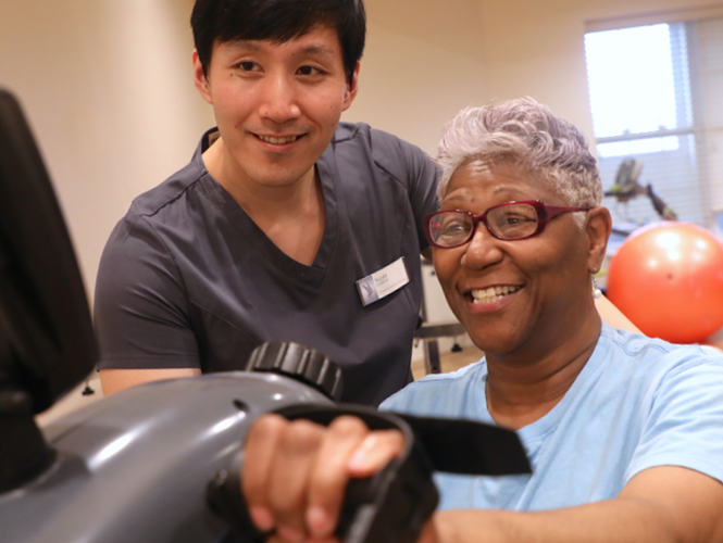 senior male senior fitness instructor assists older adult female with exercise bike