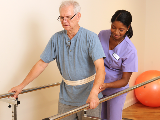 female therapist assists male senior patient with balance bars