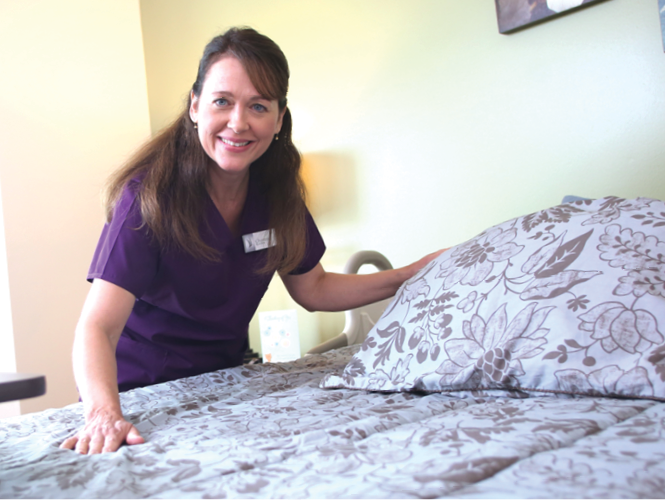 female cna makes bed where she works at providence life services