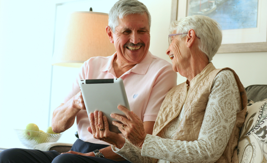 older adult couple laugh together as they look at iPad