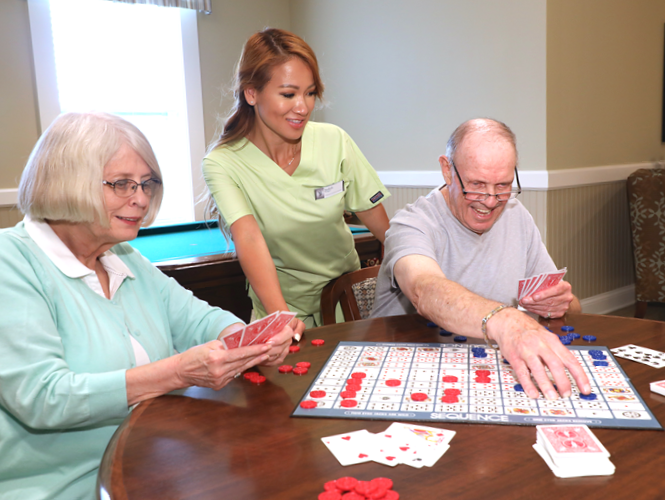 female resident aide assists senior residents playing sequence