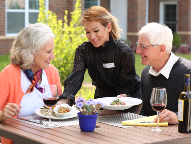 an older couple eating outdoors at park place and are served by a man