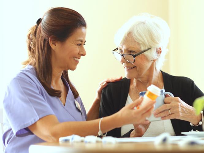female CNA assists senior older adult