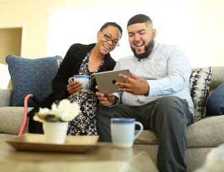 A man and a woman on a couch smiling while looking at an ipad at victorian village