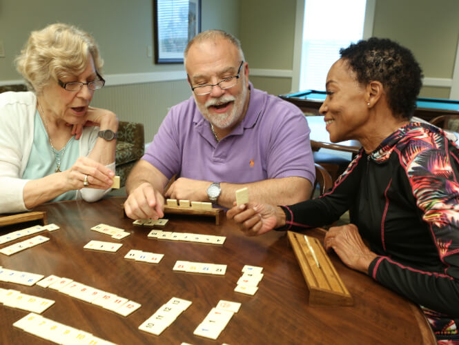 three older people playing scrabble enjoying life enrichment at victorian village