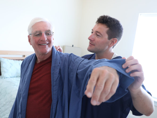 a male CNA assists male senior transition to home resident with robe