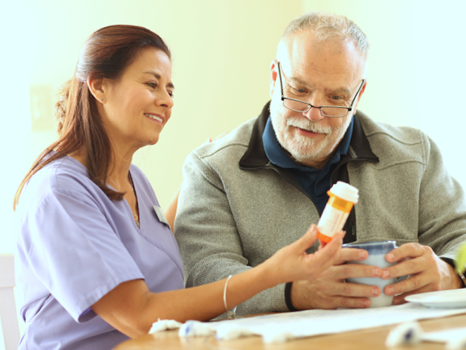 a female CNA shows medication to senior male resident