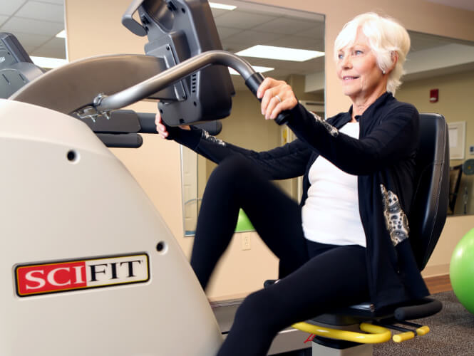 an active senior woman on exercise bike at victorian village