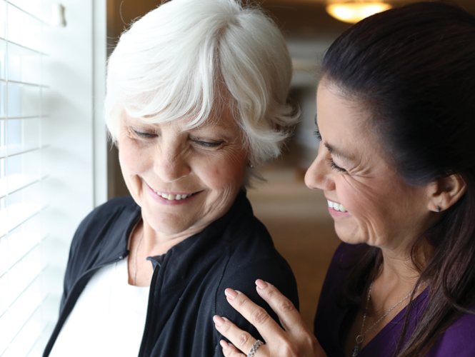 senior woman enjoys view out window as female healthcare worker speaks to her